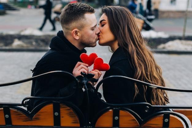 Couple amoureux s'embrasser sur un banc