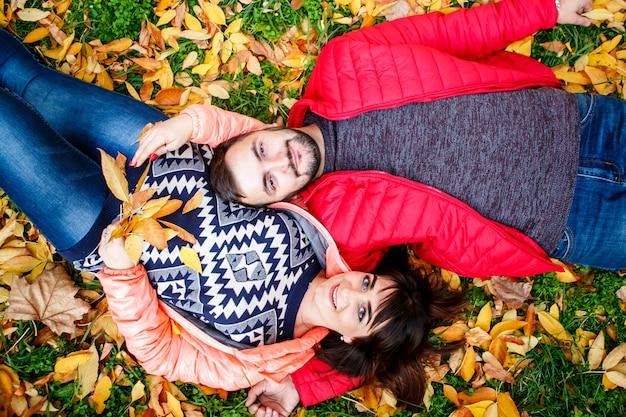 Couple amoureux se détend sur les feuilles d'automne au parc