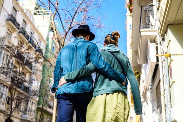 Un couple d'amoureux se promenant dans les rues alors que les touristes, habillés dans un style élégant et décontracté, s'embrassaient.