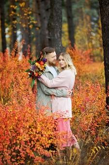 Couple amoureux se promène dans la forêt d'automne. des câlins et des baisers d'hommes et de femmes, des relations et de l'amour. jeune couple, stands, dans, jaune, herbe rouge, a, bouquet fleurs, dans, girl, main
