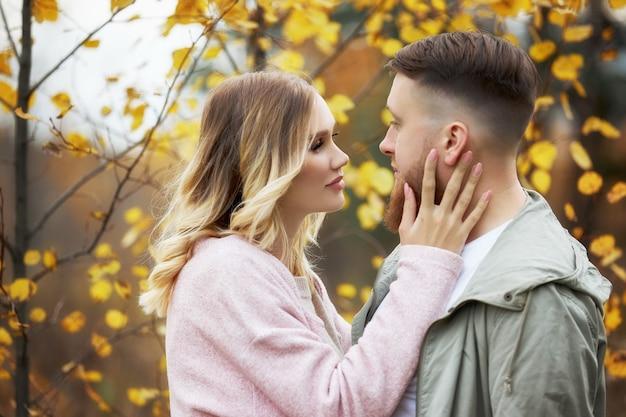 Couple amoureux se promène dans la forêt d'automne. câlins et baisers d'hommes et de femmes, relations et amour. jeune couple