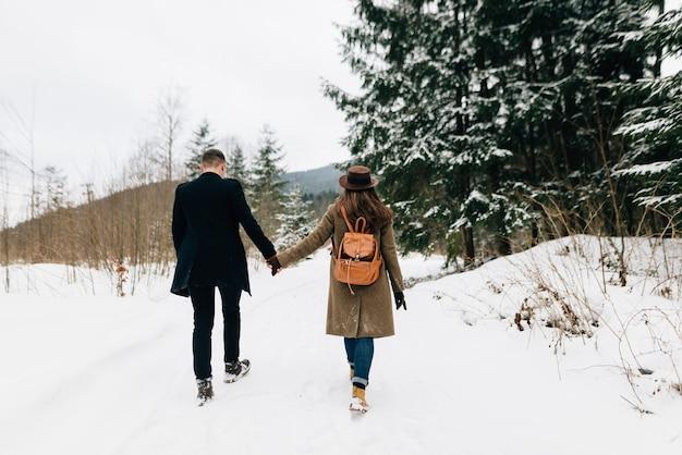 Un couple amoureux se promène dans la neige, une vue de l'arrière