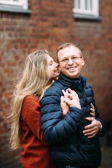 Un couple d'amoureux se promène tranquillement dans la fraîche matinée d'automne dans les rues d'un lübeck (allemagne). le gars tient sa femme dans ses bras. vacances, automne, vacances, tourisme: concept.