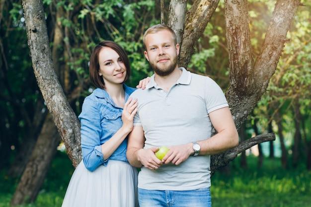 Couple amoureux se reposer en été verger de pommiers