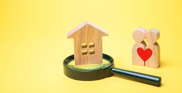 Un couple d'amoureux se tient près de la maison avec une loupe.