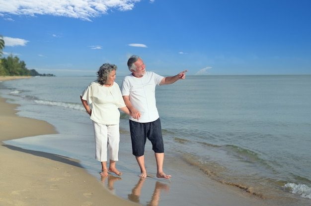 Couple d'amoureux senior asiatique voyage sur la plage. détente et loisirs en famille à l'âge de la retraite pendant les vacances d'été.