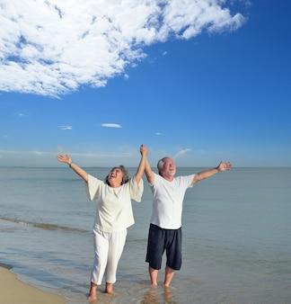 Couple d'amoureux senior asiatique voyage sur la plage. famille d'âge de la retraite détente et loisirs pendant les vacances d'été.