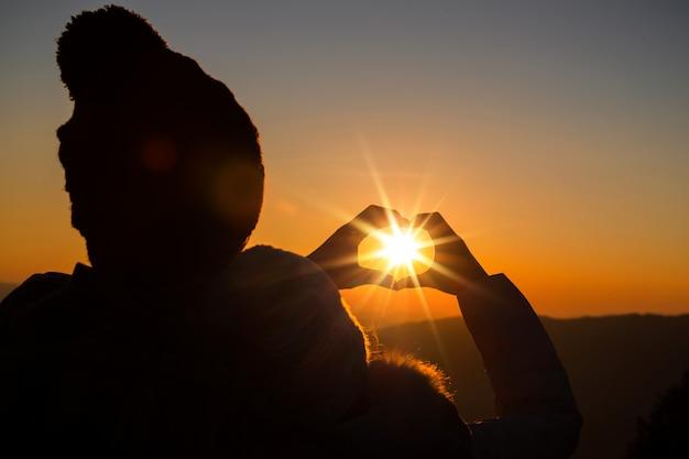 Couple amoureux silhouette rétro-éclairage sur la colline au moment du coucher du soleil