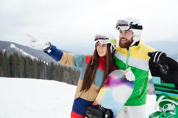 Couple d'amoureux snowboarders sur les pentes glaciale journée d'hiver pointant