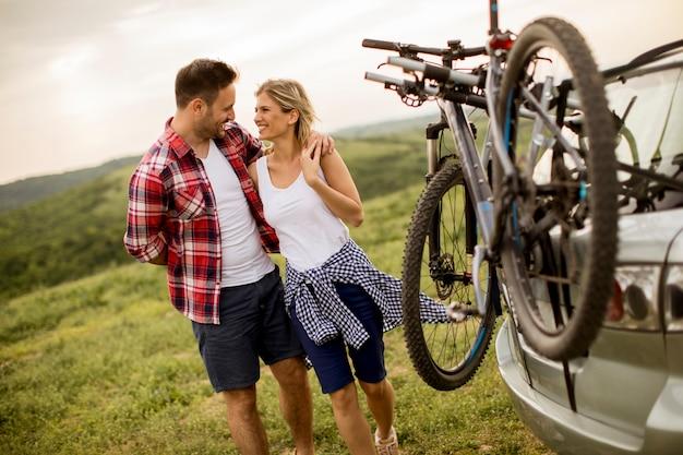 Couple d'amoureux stnding à côté de la voiture avec des vélos