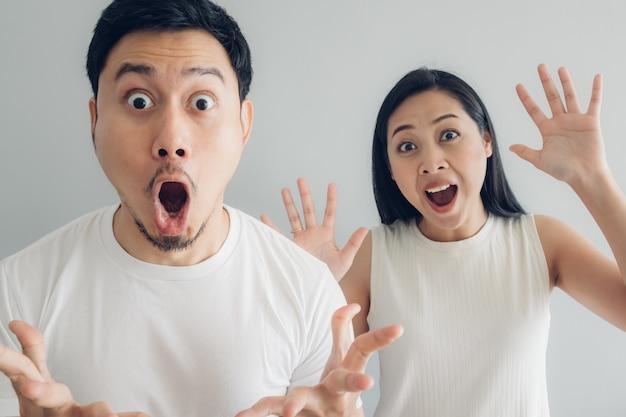 Couple amoureux surpris et choqué en t-shirt blanc et fond gris.