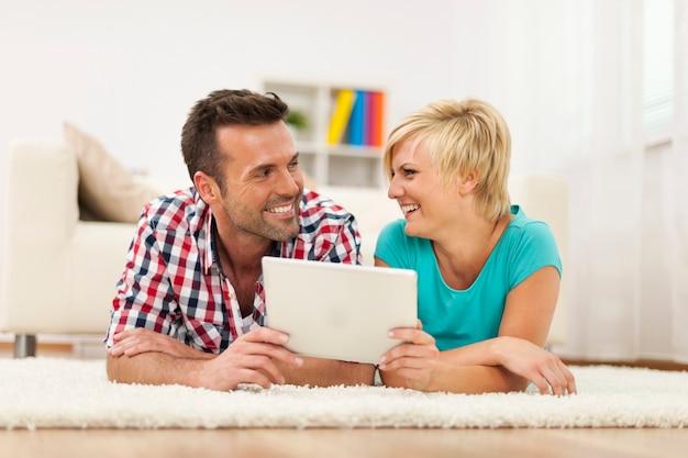 Couple d'amoureux avec tablette numérique sur tapis