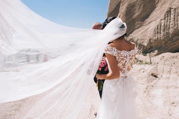 Couple amoureux, tenant mains, à, anneaux, contre, robe mariage