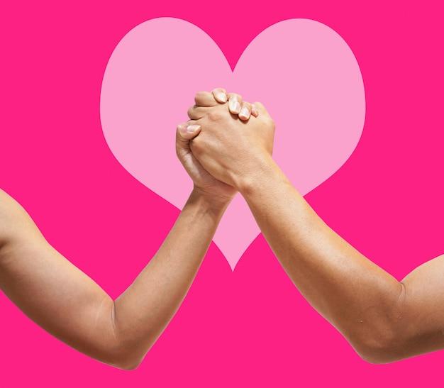 Couple d'amoureux tenant mains close-up sur coeur rose