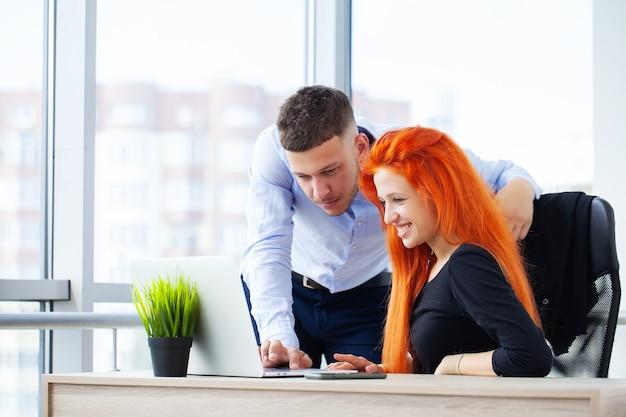 Couple d'amoureux travaillant avec succès ensemble sur leur propre entreprise au bureau.