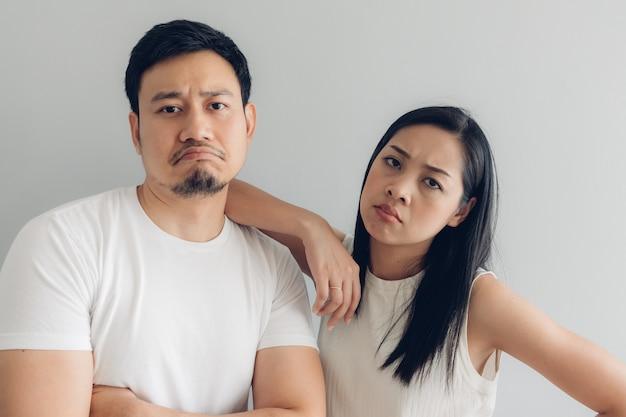 Couple amoureux triste en t-shirt blanc et fond gris.