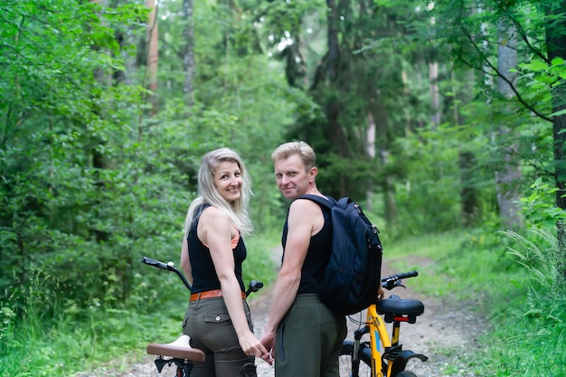 Couple amoureux sur des vélos s'amusant dans le parc