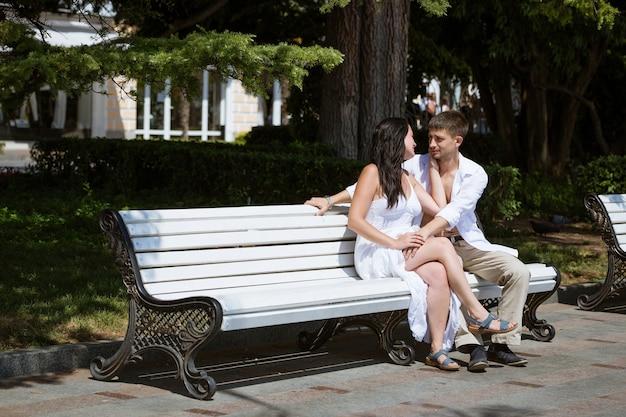 Couple d'amoureux en vêtements blancs sur un banc à l'extérieur en journée d'été ensoleillée câlins
