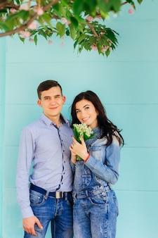 Un couple amoureux de vêtements en jean. femme tient un bouquet de fleurs