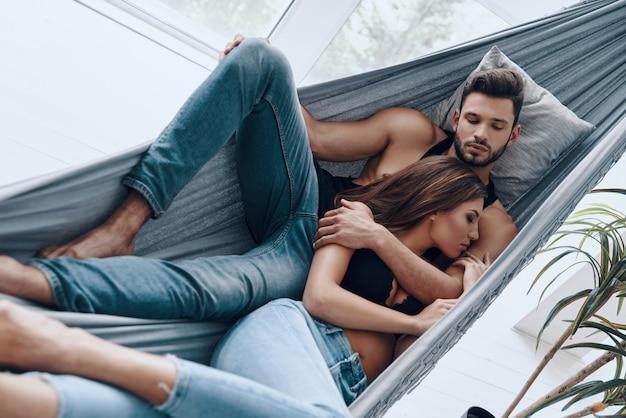 Couple d'amoureux. vue de dessus du beau jeune couple embrassant tout en dormant dans le hamac à l'intérieur