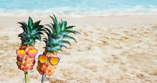 Couple ananas avec des lunettes de soleil sur le sable à la plage