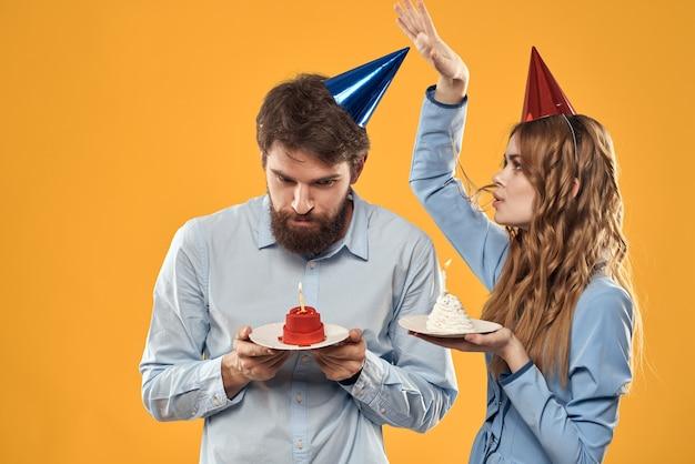 Couple d'anniversaire avec un petit gâteau et une bougie portant des chapeaux de fête isolés