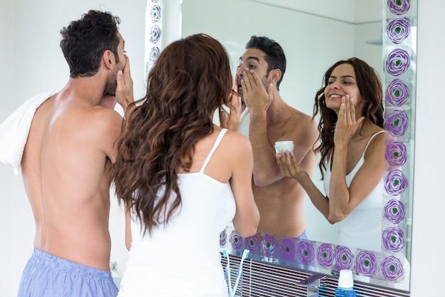 Couple, application, crème, face, regarder, miroir