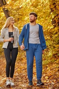 Couple appréciant la promenade dans la forêt ensoleillée d'automne, contemplant la nature, les arbres jaunes autour. randonnée, forêt d'automne, marche, concept d'amour