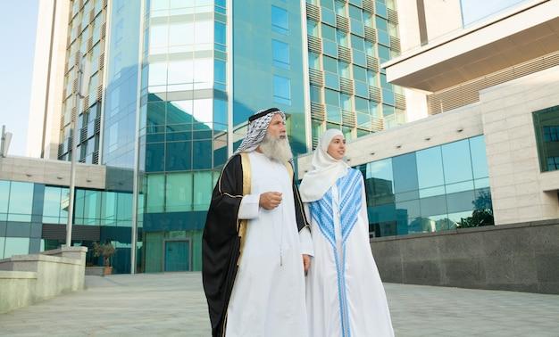 Couple arabe souriant et debout sur fond de rue