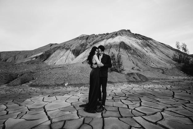 Un couple asiatique amoureux dans des vêtements en cuir noir se promène dans la nature parmi les arbres. noir blanc