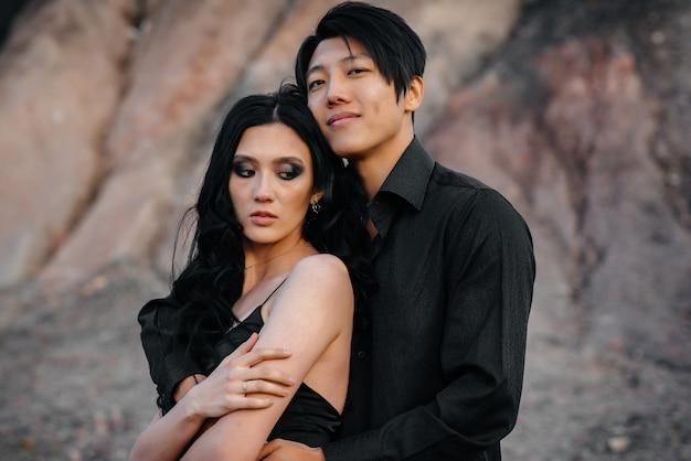 Un couple asiatique amoureux dans des vêtements en cuir noir se promène dans la nature parmi les arbres. style, mode, amour