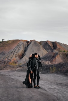 Un couple asiatique amoureux dans des vêtements en cuir noir se promène dans la nature parmi les arbres.