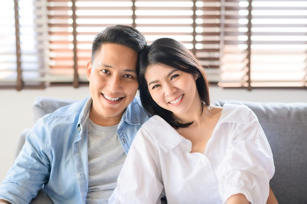 Couple asiatique amoureux souriant relaxant sur le canapé à la maison