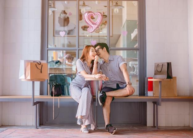 Couple asiatique assis et parlant joyeusement après le shopping.