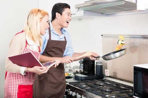 Couple asiatique, cuisson des légumes dans une poêle
