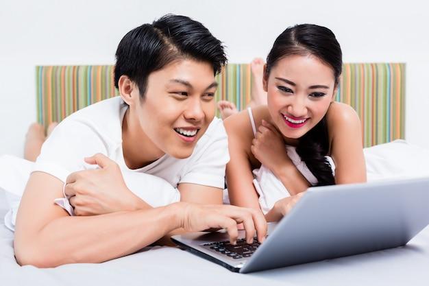 Couple asiatique dans une chambre, surfer sur internet avec ordinateur