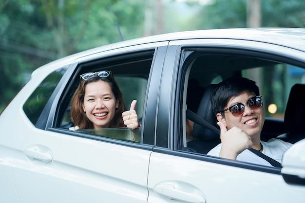 Couple asiatique dans la voiture de la ville montrent le pouce vers le haut pour la garantie