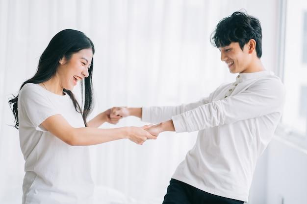 Couple asiatique dansant ensemble dans la chambre