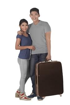 Couple asiatique debout porte valise