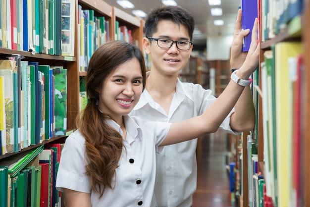 Couple asiatique d'étudiants en uniforme, lisant dans la bibliothèque de l'université.