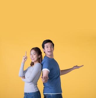 Couple asiatique excité dans des vêtements décontractés présentant les mains ouvertes pour copier l'espace isolé sur fond jaune