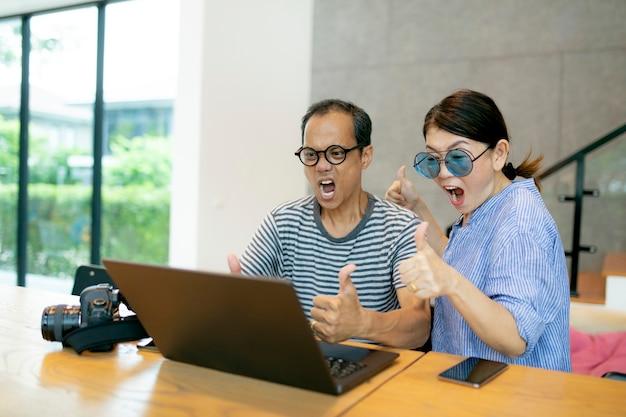 Couple asiatique avec une expression étonnée et à la recherche d'un écran d'ordinateur portable