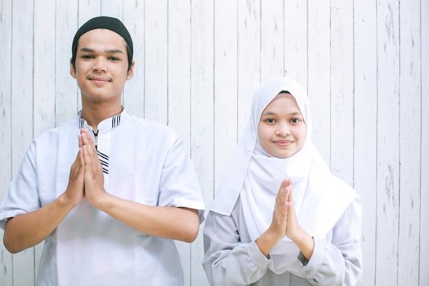 Couple asiatique faisant la poignée de main musulmane dans l'appareil photo pour la célébration de l'aïd al fitr