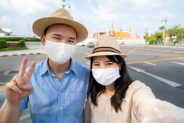 Couple asiatique heureux de voyager avec un masque pour se protéger de covid-19
