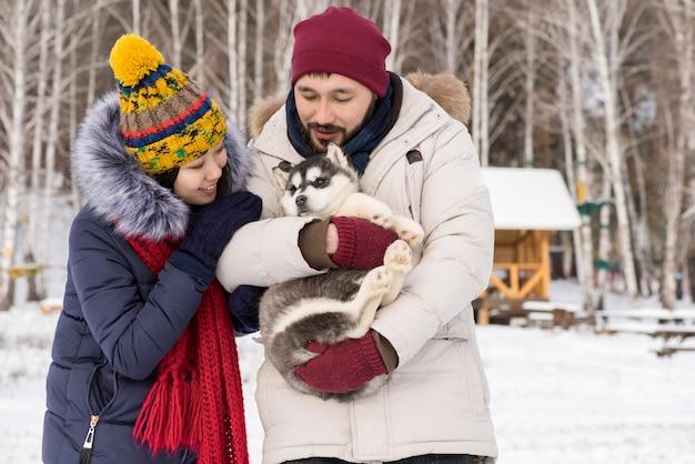 Couple asiatique jouant avec chiot husky