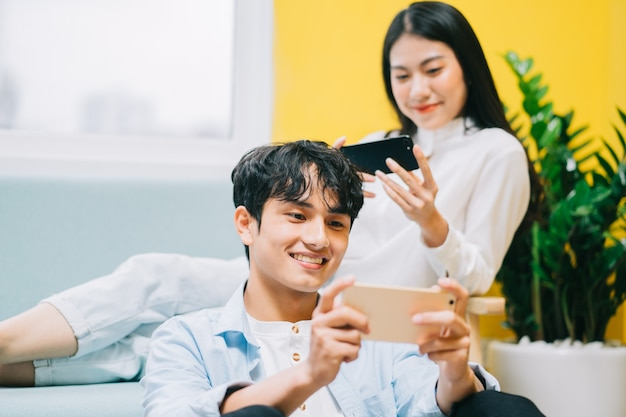 Couple asiatique jouant à des jeux à la maison ensemble, la vie heureuse d'un jeune marié