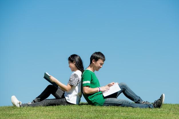 Couple asiatique, lecture livre, ensemble, à, parc extérieur