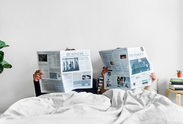 Couple asiatique, lire journaux, dans lit