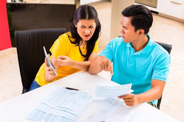 Couple asiatique lutte contre les factures impayées