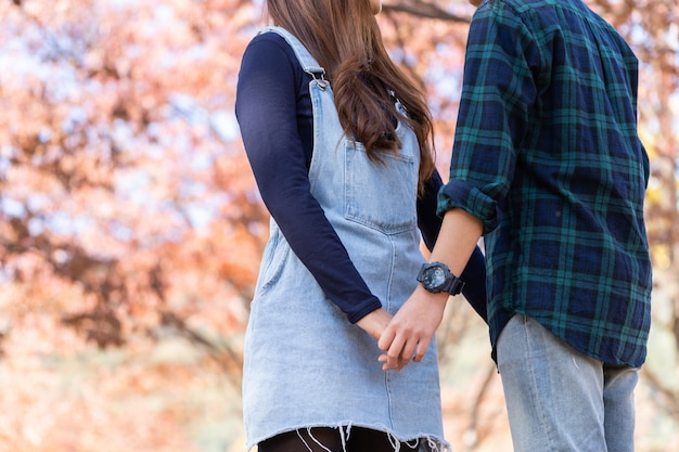 Couple asiatique, main dans la main, saison automne